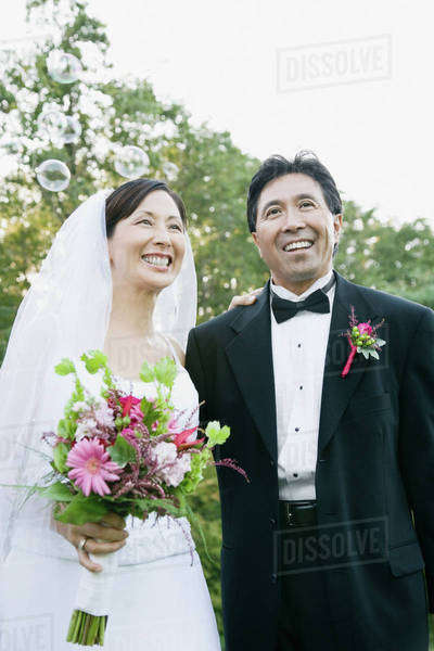 Asian newlyweds with bubbles Royalty-free stock photo