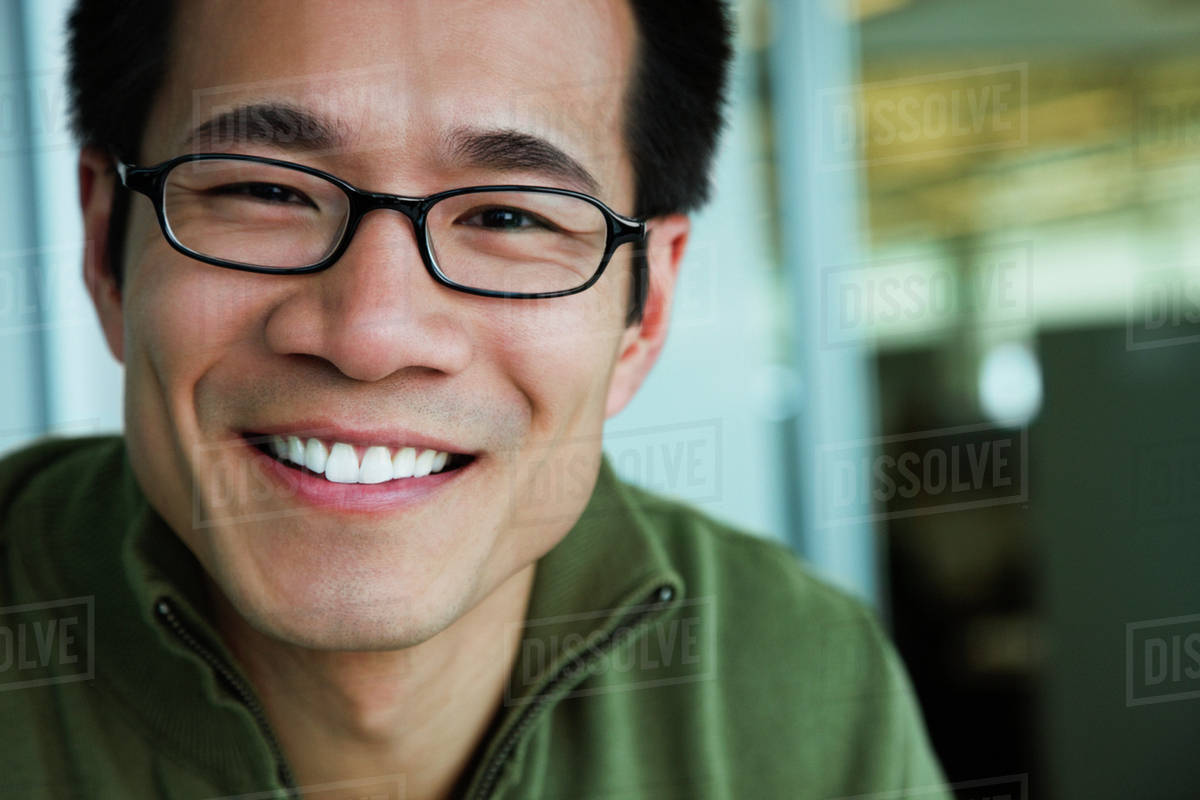 e55c9ff6cbf Close up of Asian American man wearing eyeglasses and smiling ...
