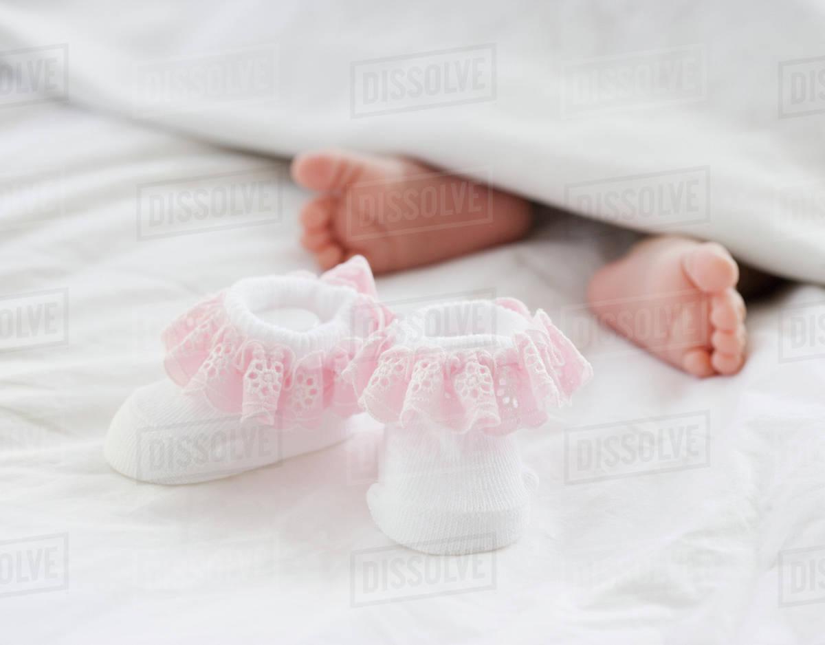 Baby booties next to newborn baby's