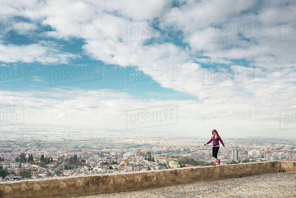 Caucasian woman on wall overlooking scenic view of cityscape, Granada, Spain Royalty-free stock photo