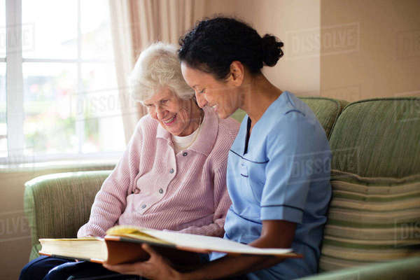 Nurse and patient looking at photo album Royalty-free stock photo