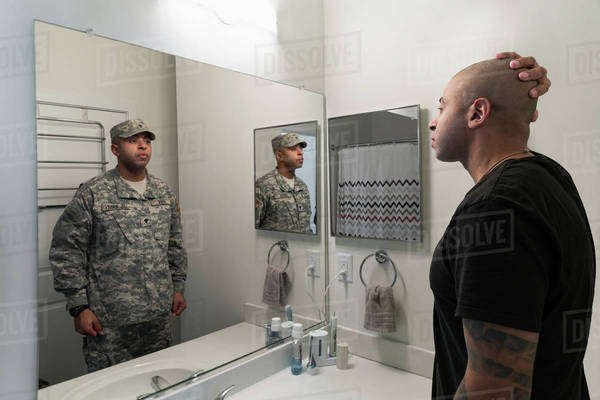 Mixed race man seeing soldier in mirror Royalty-free stock photo