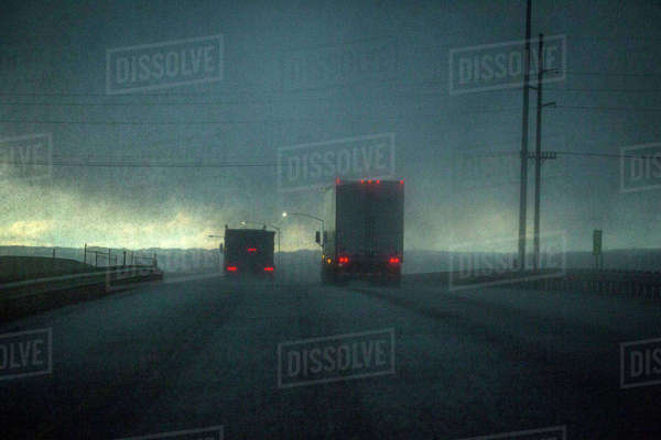 Trucks driving on stormy rural road Royalty-free stock photo