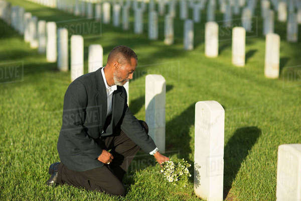 Black man kneeling with bouquet at military cemetery Royalty-free stock photo