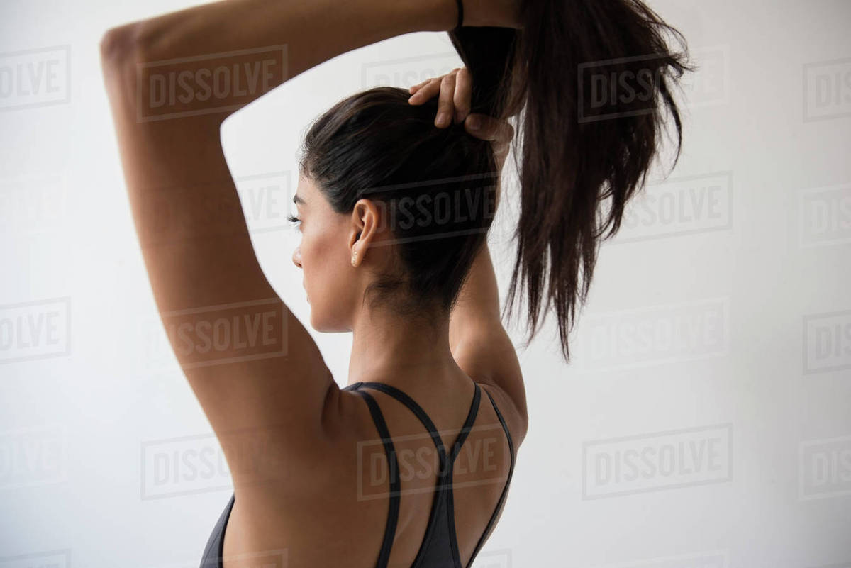 Indian woman putting hair in ponytail