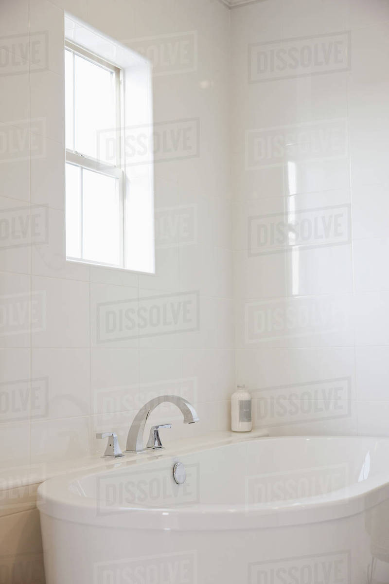 Close-up of a white bath with tiled wall and window in the bathroom ...