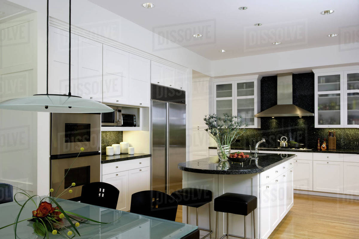 Horizontal With Frosted Glass Top Table In Foreground Kitchen Island Dark Green Black Granite Counters Stainless Steel Appliances Frosted Glass Cabinet Doors Stock Photo Dissolve
