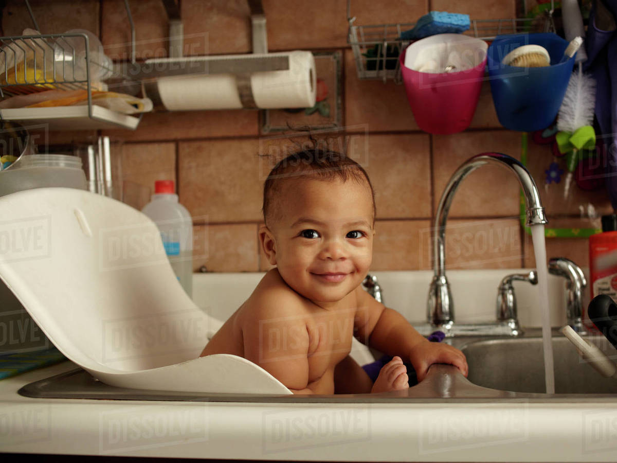 Mixed race baby girl bathing in sink - Stock Photo - Dissolve