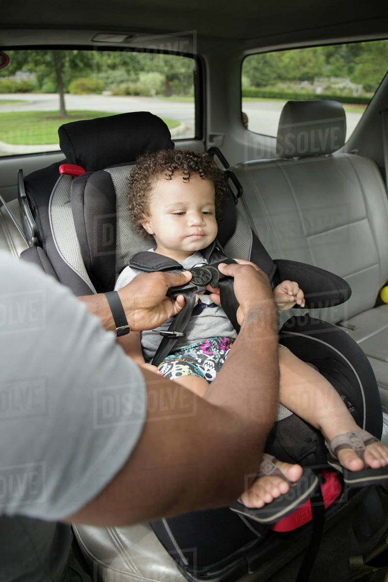 Father Buckling Toddler Son Into Car Seat