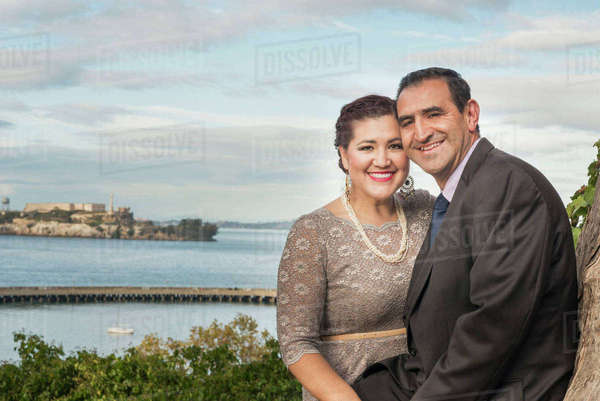 Hispanic couple in formal wear smiling near waterfront Royalty-free stock photo