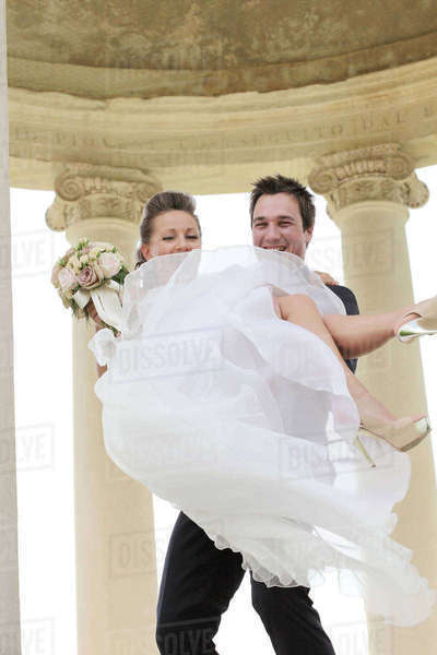Caucasian groom carrying bride after wedding Royalty-free stock photo