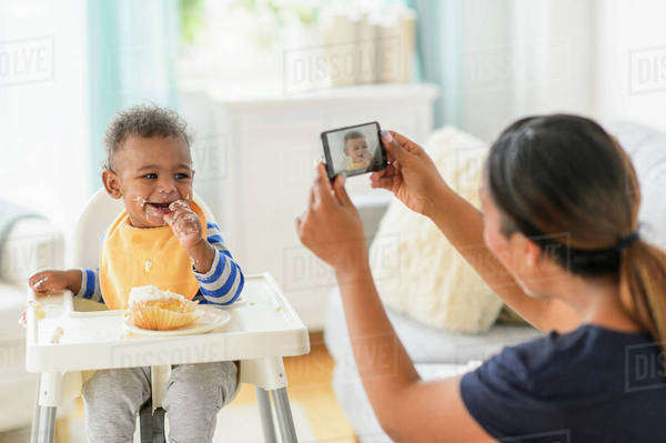 Mixed race mother photographing messy baby boy in high chair Royalty-free stock photo