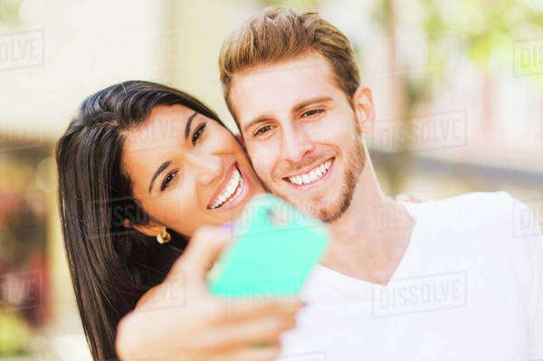 Close up of Hispanic couple taking selfie outdoors Royalty-free stock photo
