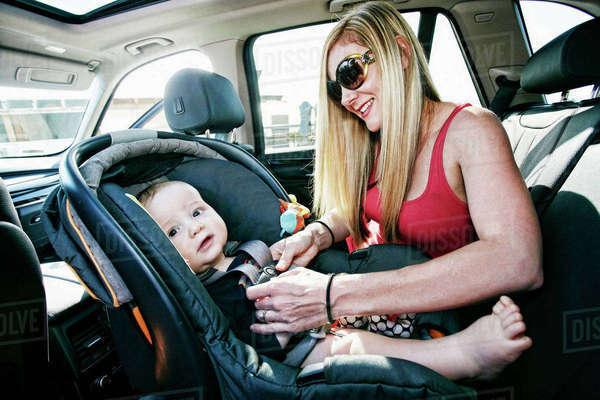 Mother buckling baby son in car seat Royalty-free stock photo