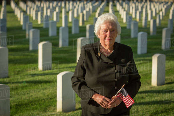 Caucasian widow holding American flag in cemetery Royalty-free stock photo