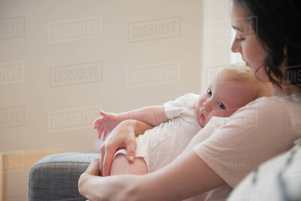 Caucasian Mother Sitting On Sofa Cuddling Baby Son