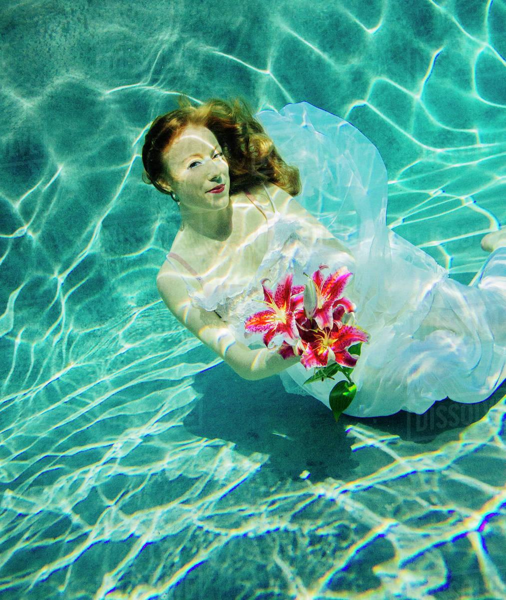 ad11f322fe Caucasian woman wearing dress holding bouquet of flowers underwater ...