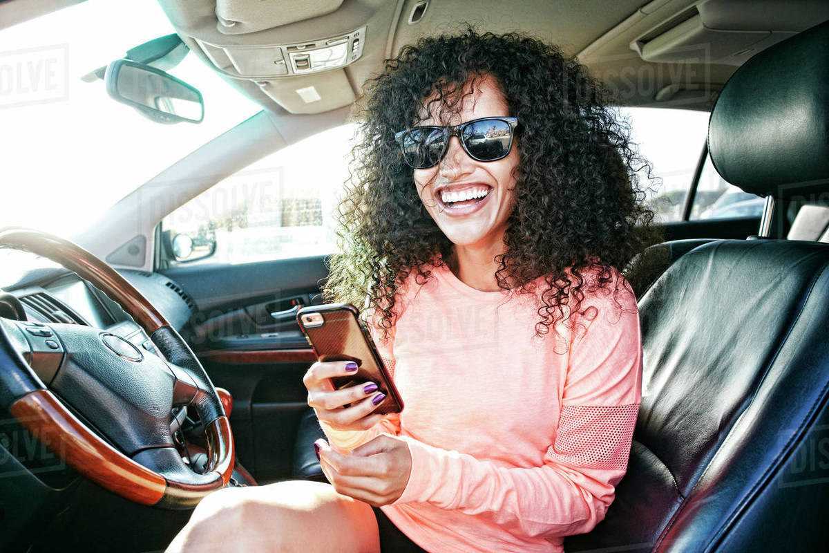 Laughing Hispanic woman in car holding texting on cell phone Royalty-free stock photo