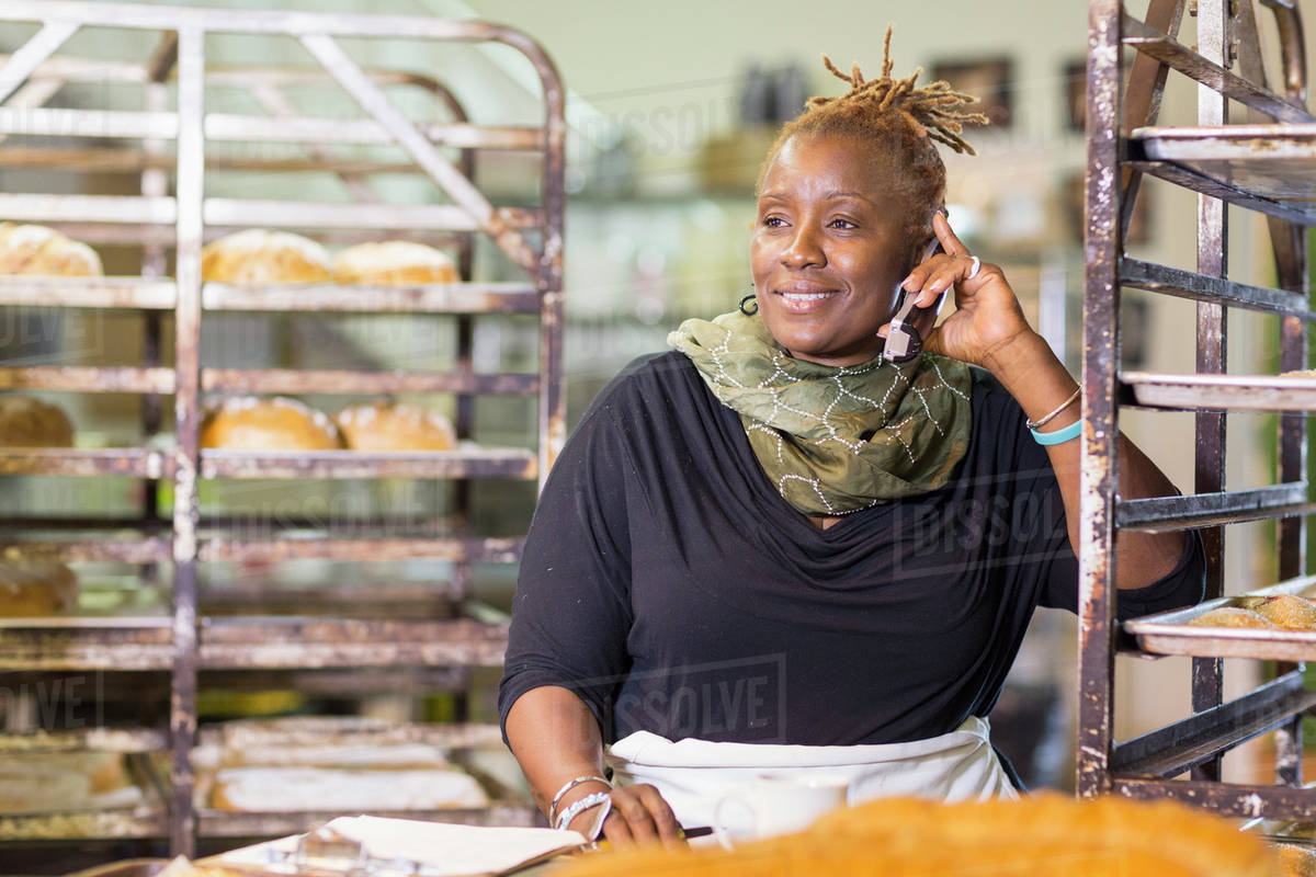 Black baker talking on cell phone in bakery kitchen Royalty-free stock photo