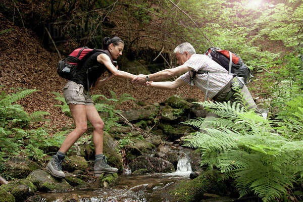 Caucasian man helping woman crossing forest river Royalty-free stock photo