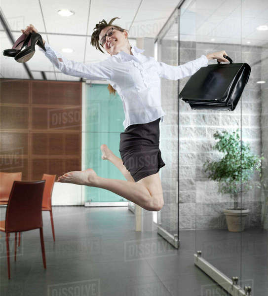 Caucasian businesswoman jumping in office Royalty-free stock photo