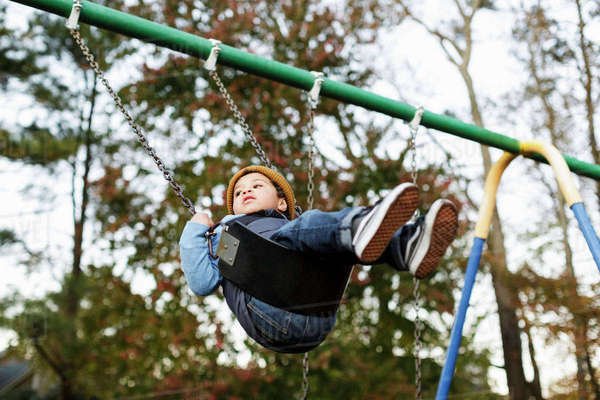 Mixed Race boy on playground swing Royalty-free stock photo