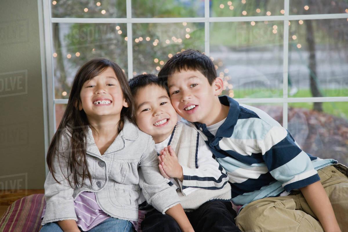 mixed race siblings hugging stock photo dissolve