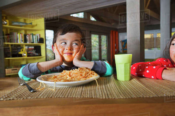 Sister watching Mixed Race brother with messy face eating spaghetti Royalty-free stock photo