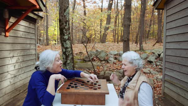Women playing checkers outdoors in autumn Royalty-free stock video