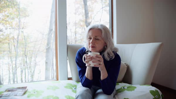 Daydreaming woman drinking coffee on day bed Royalty-free stock video