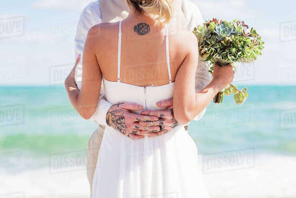 Bride and groom with tattoos hugging on beach Royalty-free stock photo