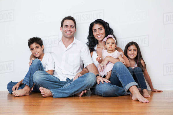 Portrait of smiling Mixed Race family sitting on floor Royalty-free stock photo
