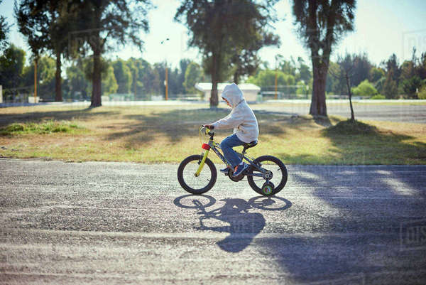Hispanic boy riding bicycle with training wheels Royalty-free stock photo