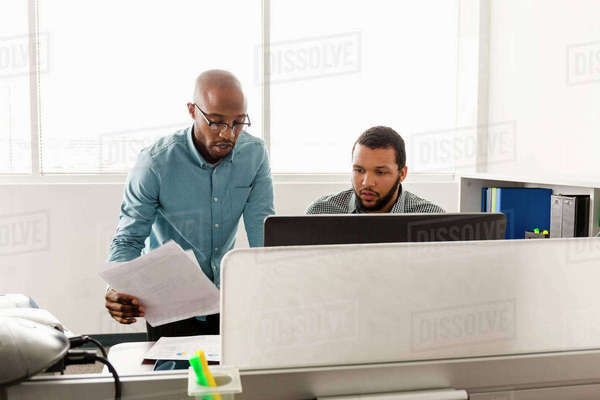 Men working at computer with paperwork in office Royalty-free stock photo