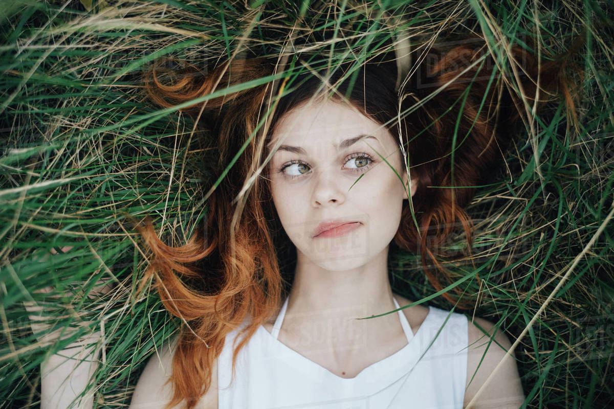 Woman Laying In Grass Blowing Hair Off Face Stock Photo Dissolve