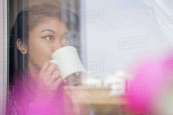 Mixed Race woman drinking coffee behind window Royalty-free stock photo