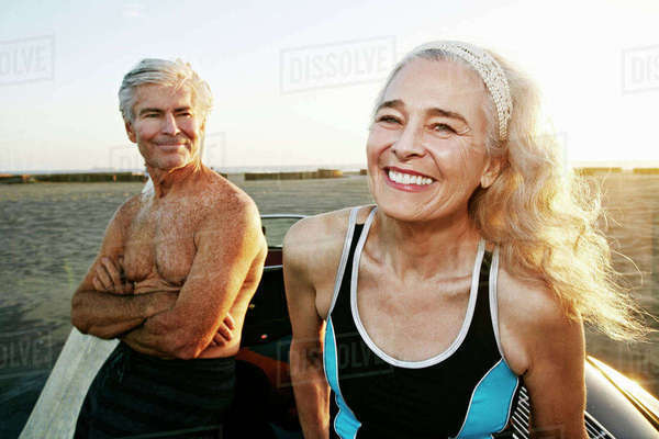Older Caucasian couple leaning on convertible car at beach Royalty-free stock photo