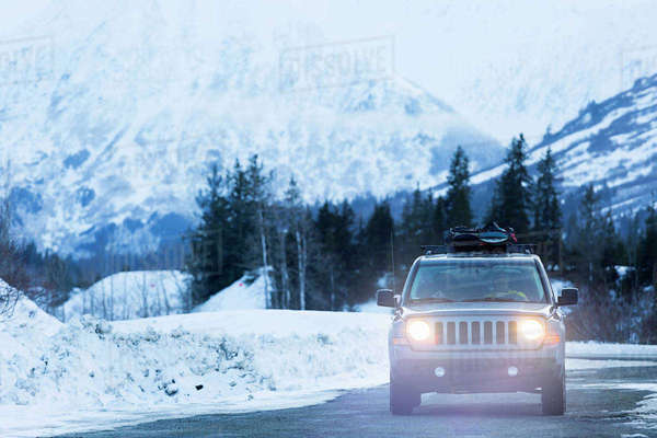 Headlights shining from car driving in winter Royalty-free stock photo