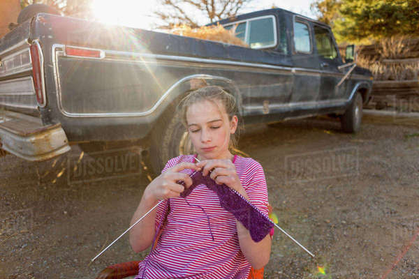 Caucasian girl sitting on chair near truck and knitting Royalty-free stock photo