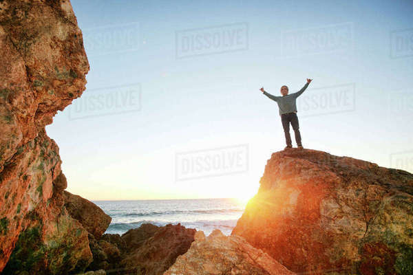 Caucasian man standing with arms raised on rock at ocean Royalty-free stock photo