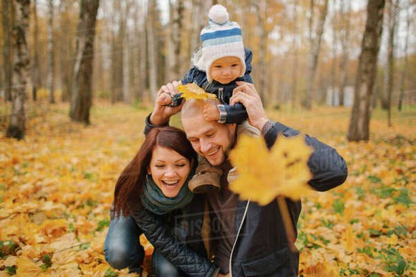 Middle Eastern couple carrying baby son in park in autumn Royalty-free stock photo