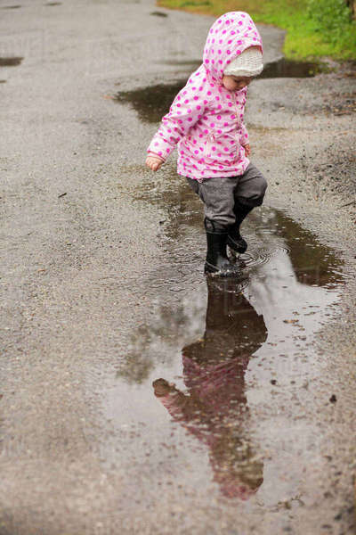 Caucasian girl wearing boots splashing in puddle Royalty-free stock photo