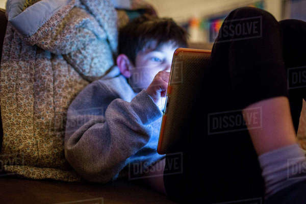 Mixed Race boy using digital tablet at night Royalty-free stock photo