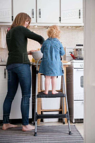 Caucasian girl standing on ladder cooking with mother in kitchen Royalty-free stock photo