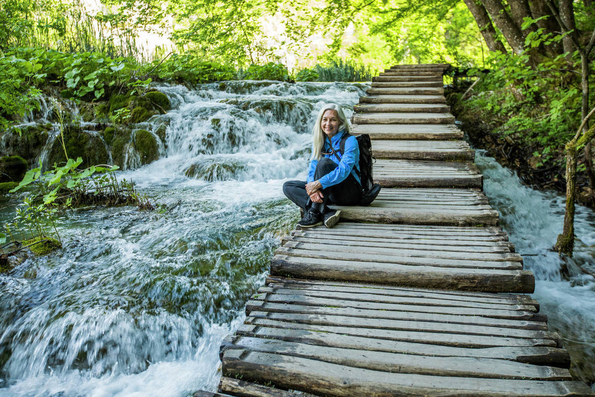 Older Caucasian Woman Sitting On Wooden Staircase Over Waterfalls Stock Photo