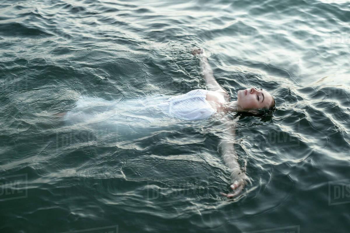 Caucasian woman wearing a dress floating in water - Stock