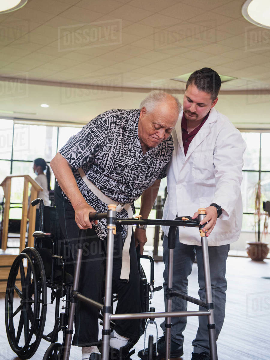 physical therapist helping man in wheelchair use walker stock