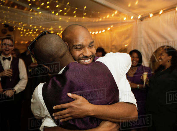 Groom hugging groomsman at reception Royalty-free stock photo