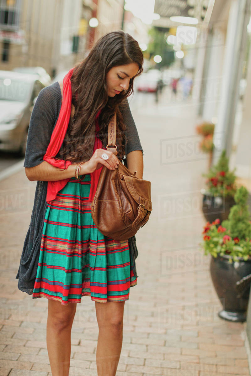 a2e68f804ed Mixed race woman digging in purse on city street - Stock Photo ...