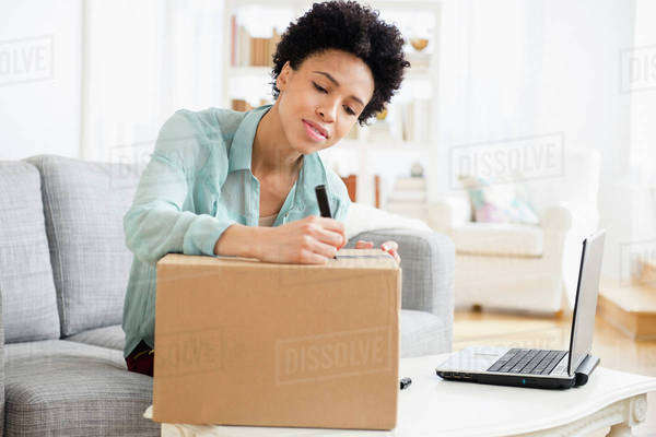 Black woman writing address on package Royalty-free stock photo